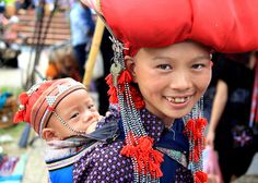 A Red Dzao woman with her baby in Sapa, Vietnam.  The tradition among the Red Dzao is for women to shave their heads when they get married.