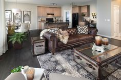 Sierra Showhome in New Brighton, beautiful brown leather couch with pattern pillows and a cozy throw - glass suitcase style tables with a printed rug and a touch of greenery