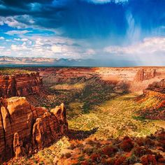 """National parks are both the stuff dreams are made of and the places where dreams come true. Evan Brogan snapped this gorgeous vista of Colorado National Monument shortly after quitting a job and asking his girlfriend to marry him. """"We took photos over the 485-foot cliff where we camped. We found ourselves at this vantage point, yelling echoes into the canyon walls, watching the rain blow in and carrying with it one of many rainbows. Photo courtesy of Evan Brogan."""