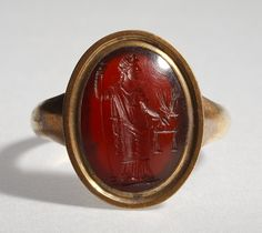 Aequitas med vægtskåle, kornaks og scepter. Hellenistisk-romersk ringsten ~~ Aequitas with scales, ears of corn and a sceptre. Graeco-Roman ringstone, 30 BC-200  Ancient carnelian stone set in a modern gold ring. 1,4 x 1,0 cm Inventory number: I605