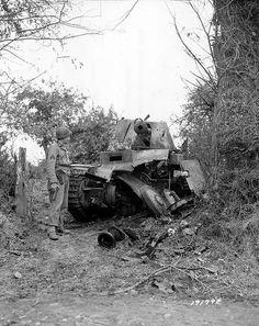 Un Sgt américain, Colt à la main pose à côté d'un Marder III Ausf. M (chasseur de char allemand) dont le train et la chenille gauche a reçu un obus explosif. Il appartiendrait à la Panzerjäger-Abteilung 352 (352 ID)
