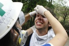 A student affected by tear gas receives medical aid during an anti-government demonstration by students in Caracas, Venezuela, April 3, 2014. REUTERS/Christian Veron