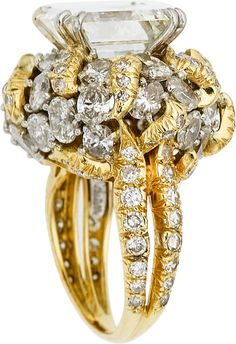 Diamond, Gold Ring, Julius Cohen The ring features a square step-cut diamond measuring 10.20 x 9.68 x 5.58 mm and weighing 4.57 carats, enhanced by oval-shaped diamonds weighing a total of approximately 3.50 carats, accented by full-cut diamonds weighing a total of approximately 0.80 carat, set in 18k white and yellow gold, marked Julius Cohen. A GIA Laboratory report # 1162603854, dated September 13, 2014, stating I color, VS2 clarity, accompanies the center diamond. Gross weight 10.53…