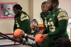 The USF football team visited patients in the Children's Medical Center - shooting hoops and sharing high fives