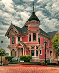 Victorian house with pink walls and a slate blue roof.