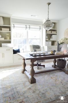 Crystal chandelier over table desk in office in front of windows and built-in cabinets in home office