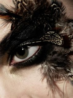 Close up of eyes with black makeup and feathers inspired by magpies from Glass Book Magazine.