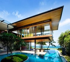 Wow , just WOW . A swimming pool by the beach (or lake). Very cool architecture. And a tree in the middle of the pool!??!! How awesome is that!