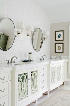 Master bathroom with white cabinetry and irridescent tile wall.