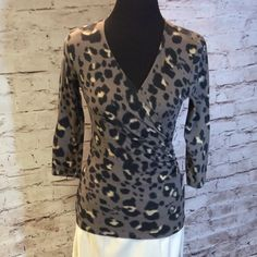 ANN TAYLOR ANIMAL PRINT BLOUSE Very pretty blouse with brown, black and white in the print. Wrap style for a perfect fit. 94% cotton 6% spandex. 3/4 sleeves.  T-1 Ann Taylor Tops Blouses