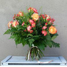 Verona es un ramo romántico en tonos anaranjados y rojizos, compuesto por rosas, claveles, bayas rojas, hipericum y verdes.