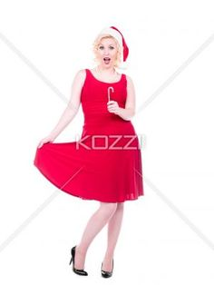 pin up christmas - Shot of a girl playing with her red dress on a white background while holding a candy cane. MUA and Model: Amanda Wynne
