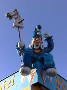 fig.: Fashionoffice's mobile phone photo was shot at the amusement park 'Wurstelprater' (means as much as 'pantaloon field') in Vienna. It shows a pantaloon sitting on a house; in one hand the jester holds a white hobbyhorse, with the other hand the figure in blue overall and foolscap with big heart on its chest is waving hello. Posted on 18 October 2013 via Twitter #1020mobilephotoday.