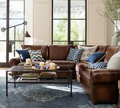 L-shaped brown leather sofa looks great and refreshed with navy and blue pillows
