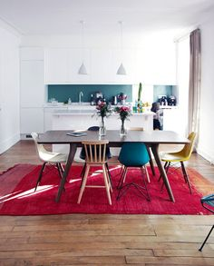 La cuisine est blanche, les chaises saluent la tendance mix and match et le tapis donne la lumière.