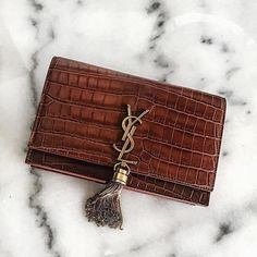 We adore this Vintage YSL #designer handbag - the tassel works perfectly with our Blenheim Collection! - Shop at Stylizio for luxury designer handbags, leather purses and wallets. Women's and Men's watches, jewelry, sunglasses and other accessories. Fine gold and 925 sterling silver rings, necklaces, earrings. Gift ideas for women and men! #womenshandbagsleathergrey