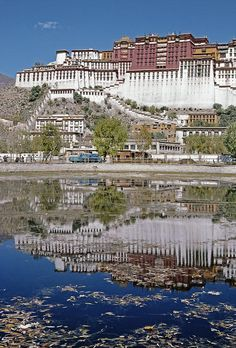 Buddhist palace is reflected in a nearby pool - Tibet