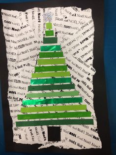 Christmas tree craft with green ribbons and pieces of paper with Merry Christmas written in many different languages.