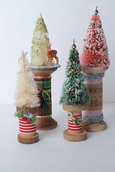 Rustic vintage wooden spools have been decorated with bottle brush trees, some vintage some new. Decorated with ribbons, holly, bells and bows they make for a cute accent to your holiday scene. Some of the spools are new some are vintage, all are adorable! The two taller spools are