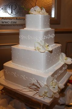 Wholesale Wedding CakeCAKE: WWC-3384 This is a beautiful ivory buttercream wedding cake with ivory buttercream pin dots and swirls on alternating tiers. (no flowers)