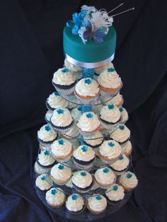 Ming/Peacock Blue Wedding Cupcake Tower - 60 Vanilla and chocolate cupcakes in silver foil papers, with vanilla BC and topped with a peacock blue blossom with edible white hologram glitter in centre of each.  Top cake is a 5 inch chocolate cake, covered in chocolate ganache and thin layer of peacock blue fondant, with silver ribbon. Cake topper was provided by the 80-year-old bride and groom! Acrylic cake stand decorated with peacock blue ribbon on centre pillar. Thanks for looking!