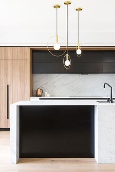 A sleek, modern kitchen that has all the elements a fabulous kitchen needs - marble, black, warm wood and statement pendants. Another dreamy project (award-winning to boot) by Minosa.