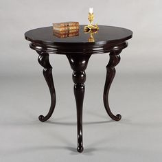 "Erika Brunson  Segmented scrolled legs support a round top inlaid with Macassar Ebony veneer  Dimensions      30"" dia x 29""h"