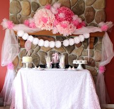 Pretty pink Princess Birthday Party table setup with a cute banner and flowers above.