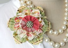 Love this flower on the necklace, great textures and colors coming from fabric choices.