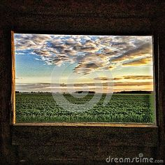 Hunters view from its closed cabin. Image taken from the inside with the frame of the wooden window in front.  Storm clouds are  hanging deep from sky above. Image taken as a hdr with colour and compression. The sun is going down and makes beautiful colors on the sky and field.