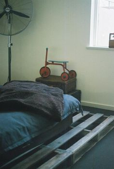 ...to add a bitt more colour to the room i found a 1940's tricycle which i have placed upon 1960's brown and black leather suitcases.   ... the concept of the oversize industrial fan in the room works well with the pallet bed base and remaining wood through the room.