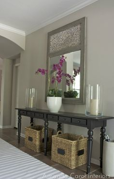 Pop of color with orchid on console table.  Good mixing of textures (ceramic, wood, rattan, cotton rug, glass, mirror)