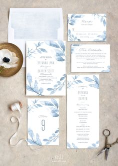 Gorgeous dusty blue wedding invitation suite with blue painted leaves.