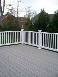 A grey solid color stain on this deck looks great with the white railing and posts. Two-color combos look fantastic on decks. For deck finishing in Bellingham WA, visit www.
