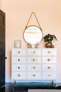 Interior designers say white lacquer furniture is worth the splurge when decorating your home like this dresser from Anthropologie.