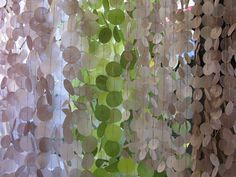 GORGEOUS! Wax was spread between layers of different colored tissue paper and ironed together to create translucent sheets. Circles were cut and strung together to create intersecting blocks of color - Designed by Anthropologie Visual Team