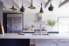 black and gold pendant lights, white kitchen island, wood rafters Tom Dixon