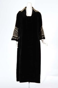 1923 Black velveteen evening dress.Center front panel effect is created by two vertical pleats with horizontal tucks every 3.5 inches, creating a ladder effect from neck to hem. Back flanges start at shoulder seam and are released at the dropped waist level. Back waist line is shirred from the flange to the side seams. Collar and flared sleeves are elaborately trimmed with couched silk cording.