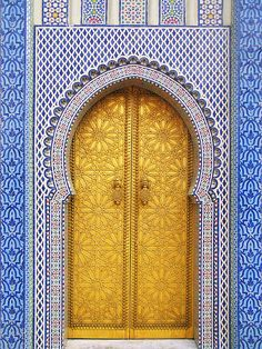 Dar El Makhzen, Fez, Morocco, Tile in various shapes and shades of blue and white surround gold double door in keyhole opening