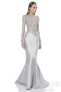 Elegant long evening gown with jewel floral lace applique bodice. This formal evening gown is finished with a jewel encrusted waist detail.