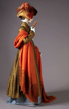 """Isabelle"", from the exhibition ""Napoleon and the Empire of Fashion"". Lancaster-Barreto collection. Pelisse: Moss green silk taffetas pelisse with sky blue silk lining and Point de Bruxelles lace collar, French or English, ca. 1811. Pumpkin-colored cashmere shawl, Indian, ca. 1810. Gold brooch with sea shell cameo and paste jewels, English/Italian, 1812-1815."