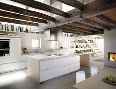 Nos encantan las cocinas abiertas al salón como esta, lacada en blanco y sin tiradores contrastando con las vigas de  madera a la vista.