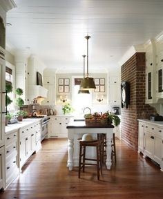 I love the exposed brick on the right and the island with the pendant lights