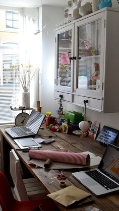 glass doors on the cabinet let light bounce and add charm to this home office