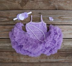 So, so cute!  1 piece or 4 piece set....BUILD her outfit!  Select just the dress....Dress and headband...or a complete outfit of dress, headband, pearl necklace and flower bracelet.    This purple petti dress is super soft and fluffy! Chiffon petti skirt LOADED with ruffles....she will LOVE wearing this! The headband is made using purple and white silk flowers with a small purple satin flower on a white elastic headband.    The rosette top is attached to the skirt.    **Please indicate the…