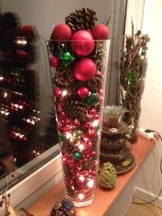 Kerstballen, dennenappels, led-verlichting in grote vaas.