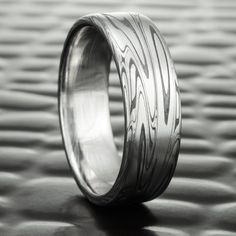 This SWIRLING CURRENT Damascus band, features a strong river of stainless steel. It has a powerful, organic design wrapping and spiraling around the band like a swirling river. The dark Fire Oxide makes each line bold, creating an eye catching masculine ring, that tells a compelling visual story. The SWIRLING CURRENT happens to be one of our most technically demanding rings to make, requiring many different operations to coax the pattern from the material. That is why it is one of our…