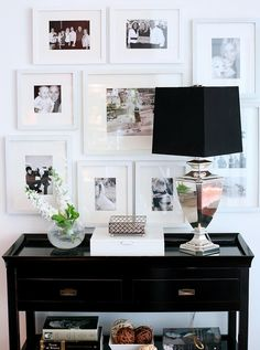 white-frame picture wall with contrasting black furniture for an entry way
