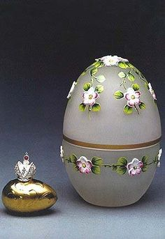 (3) FABERGE eggs__Theo Faberge__ Spring Egg. Seeks to unravel the mystery of the egg and its symbolism of life and rebirth. The delicate hand painted enamelled spring flowers raised from the crystal surface express the regeneration of nature after Winter, when the land will once again blossom and bear fruit. The surprise is a golden yolk upon which is set the Imperial Crown in sterling silver, which reveals a hidden compartment.