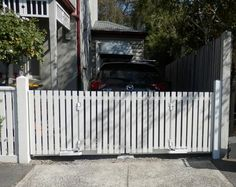 Bi-fold trackless automatic gates. Timber picket style. Perfect for this drive with no room for a standard swing or sliding gate. www.themotorisedgatecompany.com.au
